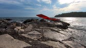 Red sunchair on stone coast against stormy sea, cloudy blue sky, green island. Vacation, relaxation, recreation concept. Empty lounge chair on beach, oncoming sea waves washing-down rocky seashore Stok Video