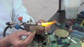 Lampworking. The artist makes jewelry from glass using a gas burner.
