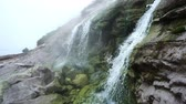 onsen : White vapor rises above hot waterfall on geothermal riwer on the slope of the volcano. Kuril Islands, Itutrup Island, Baranskiy Volcano. Slowmotion 240 FPS