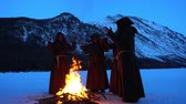 rite : Four monks pray at the campfire in the mountains slow mo