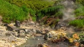geotérmica : Hot drops of water slowly fall in the stream of the geothermal river on the slope of the volcano. Kuril Islands, Itutrup Island, Baranskiy Volcano. Slowmotion 240 FPS