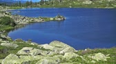 selvagem : Panorama of a blue mountain lake surrounded by wooded peaks. Western Siberia, Ergaki range.