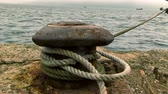 demir : Rusty, old bollard with a rope that fixes a ship in an harbor Stok Video