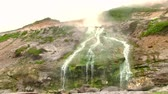 yellowstone : Hot drops of water slowly fall in the stream of the geothermal river on the slope of the volcano. Kuril Islands, Itutrup Island, Baranskiy Volcano. Slowmotion 240 FPS