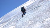 экспедиция : Side view of a mountain climber climber going up icy slope with rope Стоковые видеозаписи