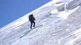 góral : Side view of a male mountain climber going up icy slope with rope
