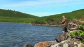 A man with a spinning catches fish in a lake against green mountain. Kuril Islands, Okhotsk Sea Stock Footage