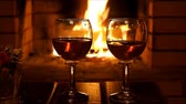 Two glasses of wine on the background of a burning fire in the fireplace Vídeos