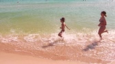 Happy children run for dad along the edge of the sea. Slow motion.