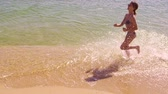 Happy family running along the edge of the sea. Slow motion. Dostupné videozáznamy