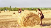 Two cute girls run around and play a haystack. Slow motion.