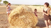 Two cute girls and a little boy run around and play a haystack. Slow motion.