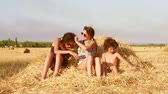 곤포 : Two cute girls and a little boy play on a haystack. Slow motion.