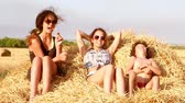 Two cute girls and a little boy play on a haystack. Slow motion.