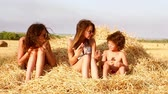 bratr : Two cute girls and a little boy play on a haystack. Slow motion.