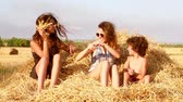 Two cute sisters and a little brother playing on a haystack. Slow motion.