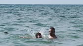 Dad and son are resting on the sea. Dad teaches his son to swim. Dostupné videozáznamy