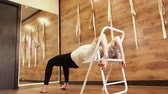 Yoga teacher practicing in studio with wooden walls and floor. Yogi using chair for parsvottanasana pose. Helpline posture, slow motion Dostupné videozáznamy