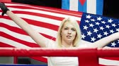 participante : Success woman celebrating her success with the flag of USA. Female boxer with flag Patriot and fan concept. slow motion Stock Footage