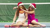 esportivo : Two sexy brunette girls in glasses sitting on the court. Celebrating the new year during a sporting event. Sporty girls Christmas. slow motion