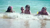 criança : Parents and children lying in water at the sea shore. Family have fun playing with sea waves. Slow motion