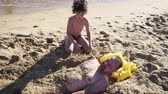criança : 4K Father Plays With His Little Boy At Beach, Little Son Is Buried In Sand, Cute Moment Slow Motion