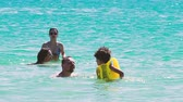 criança : 4K Happy family of four in vacation at sea shore. happy mum daddy and two children play in water.