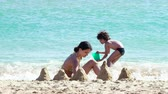 criança : 4K Children make a castle of sand on the beach. Two siblings of different ages, brother and sister, sitting close to the sea and digging in the sand on hot day at the beach