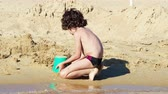 criança : 4K Little boy playing with sand at beach in summer holiday Vídeos