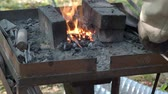 плоскогубцы : village blacksmith heated the iron rod in burning coals in forge before forging in rural smithy