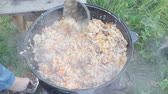 pilau : top view of stirring the plov (central asian rice dish with meat and catrrot) in kazan pot on an outdoor oven