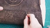 cucire : workshop bag making the carved leather bag - craftsman sews the flap to the leather handbag Filmati Stock