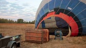 Big balloon being filled with hot air on the ground before flight