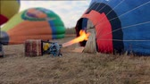 Propane gas burner filling balloon with hot air on the field Stock Footage