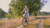 Beautiful younhg woman riding bicycle on sunset at field
