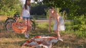 Young mother with daughter having picnic under big tree after riding bicycles Stock Footage