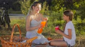 Happy young mother sitting with daughter under tree and drinking orange juice Stock Footage