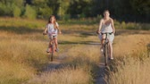 Young woman riding with girl on bicycles in the filed at sunset