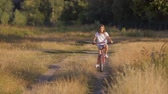 Happy young girl riding bicycle through big field at sunset