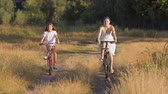 Beautiful young woman with girl riding bicycles in field at countryside