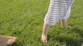 Closeup shot of young mother teaching her baby son how to walk on grass at park