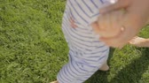 View on babys legs running on grass with mother