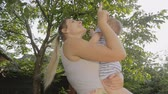 Happy young woman kissing and cuddling her 1 year old baby son Stock Footage