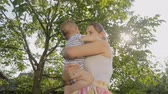 Portrait of young mother cuddling her baby at tree shade Stock Footage