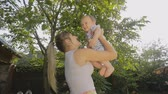 Happy young mother holding her baby son high up at the orchard Stock Footage
