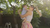 Cheerful young mother with baby standing under tree at sunny day Stock Footage