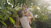 Happy cheerful woman lifting her baby son under tree at orchard Stock Footage