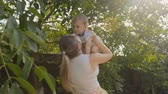 Young smiling mother lifting her baby son under tree at park Stock Footage