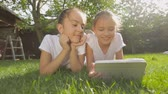 Portrait of two smiling girls lying on grass and using digital tablet
