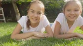 Dolly shot of two smiling girls lying on grass at park Stock Footage